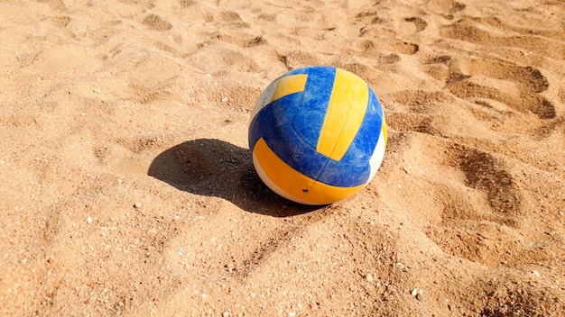 Closeup photo of volleyball ball lying on the sand at sea beach