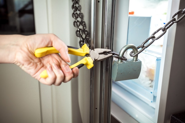 Closeup photo of woman cutting chain on fridge with pliers