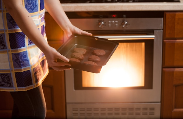 Closeup photo of woman putting cookies in oven