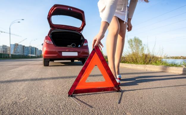Closeup photo of woman putting warning sign after car crash
