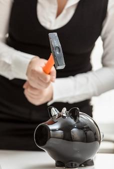 Closeup photo of woman smashing black piggy bank with hammer