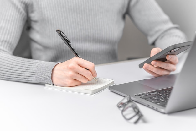 Closeup photo of woman working with laptop and writing in notebook.