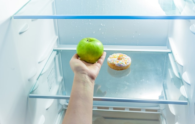 Closeup photo of women hand holding apple instead of donut in refrigerator