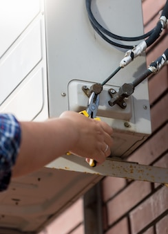 Closeup photo of worker connecting pipes to air conditioning system