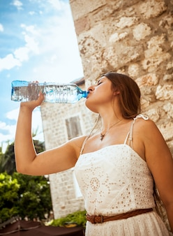 Closeup photo of young brunette woman drinking water out of bottle at sunny day