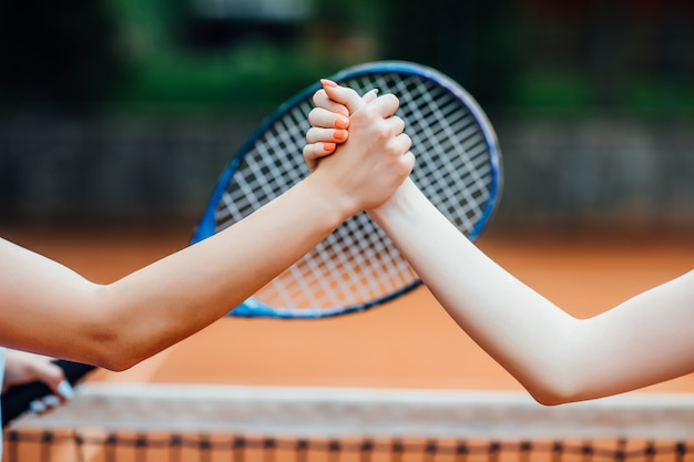 Closeup photo. young girls shaking hands on tennis court, smiling.