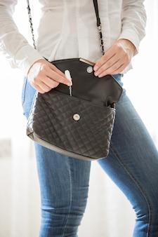 Closeup photo of young stylish woman taking tampon from handbag