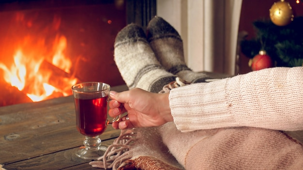 Closeup photo young woman drinking tea under blanket next to fireplace