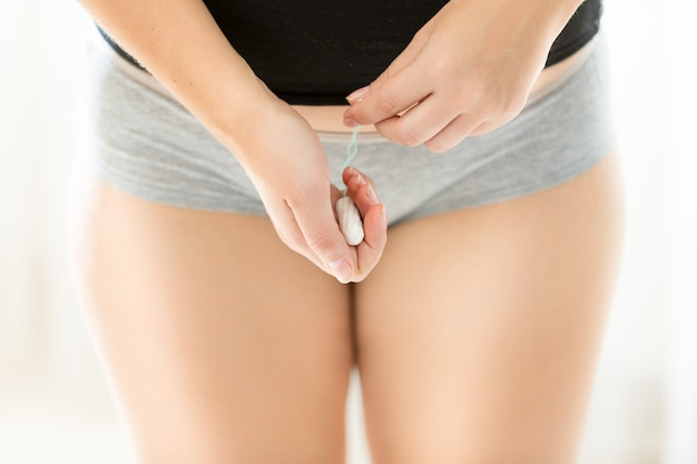 Closeup photo of young woman in lingerie holding hygienic tampon