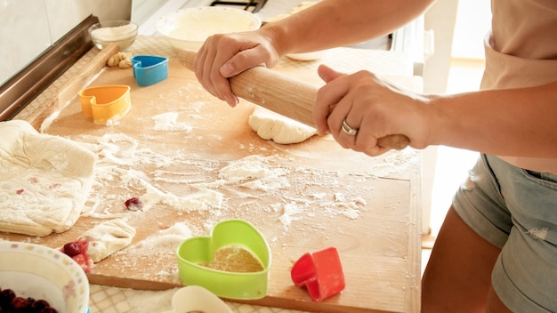 Closeup photo of young woman making dough for pizza