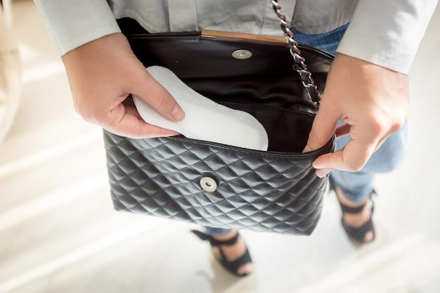 Closeup photo of young woman putting menstrual pad out of handbag