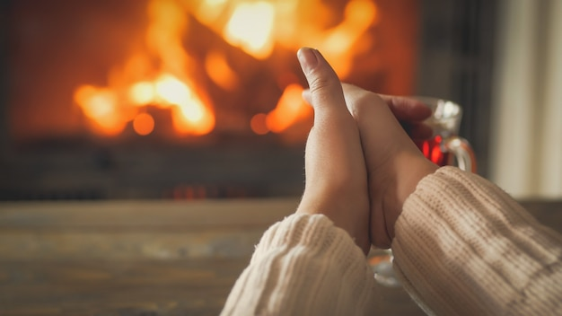 Closeup photo of young woman warming hands by the burning fireplace at house