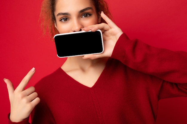Closeup photo of young woman wearing dark red sweater isolated over red background holding