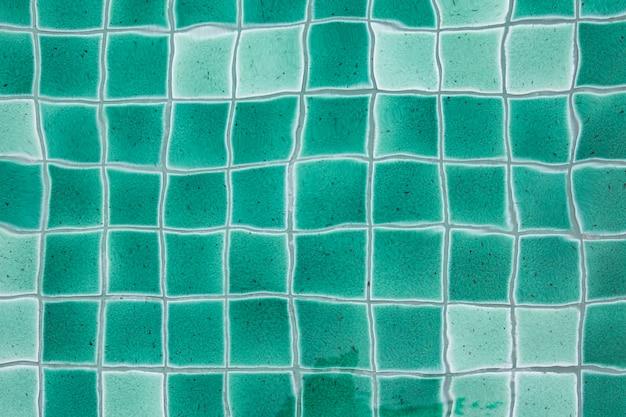 Крупным планом фотографии зеленой керамической плитки текстуры фона под водой бассейна