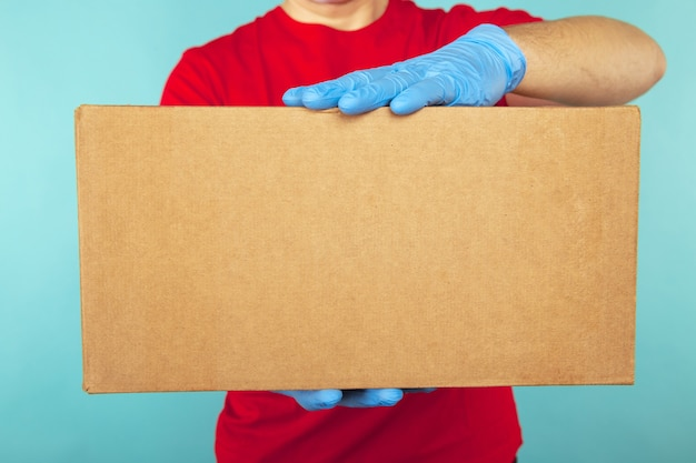 Closeup picture of delivery man in blue gloves holding carton box.