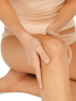Closeup picture of female hands touching knee