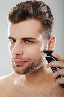 Closeup picture of good-looking adult guy grooming his face with shaving his cheek using electric shaver over grey wall