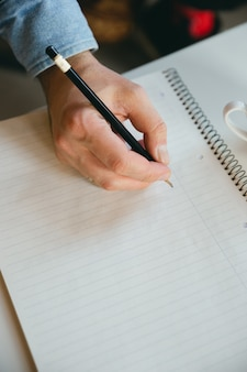 Closeup picture of a hand writing with a pencil on a blank notebook.