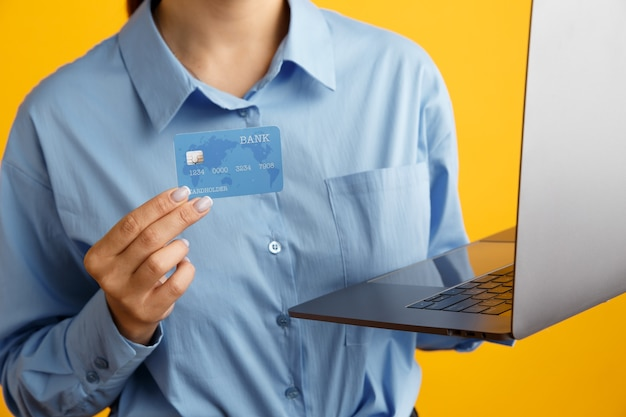 Closeup picture of laptop and shopping credit card in woman's hands.