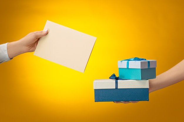 Closeup picture of man and woman's hands with gift box on yellow background