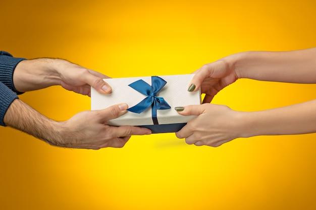 Foto primo piano di mani di uomo e donna con confezione regalo su sfondo giallo