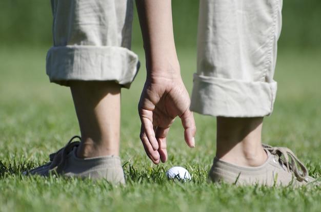 フィールドでホワイトゴールドのボールを取っている人間のクローズアップ写真