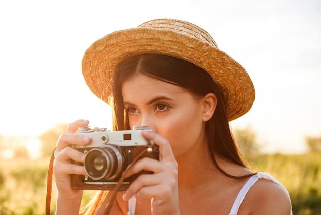 Снимок крупным планом красивой молодой женщины с длинными темными волосами в соломенной шляпе, фотографирующей на ретро-камеру, отдыхая на солнечной природе