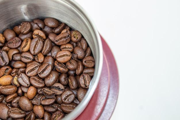 コーヒー豆挽き器とコーヒー豆のクローズアップ写真。