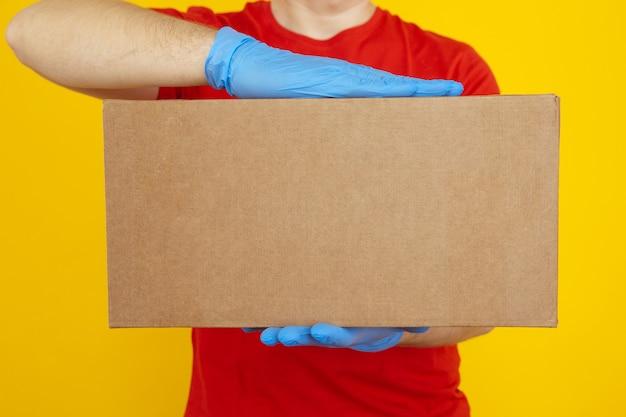 黄色の上にカートンボックスを保持している青い手袋の配達人のクローズアップ画像