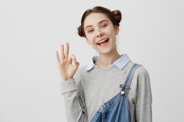 Изображение крупного плана симпатичной женщины показывая хорошо с пальцами смеясь над в радости. взрослая самка тренера радуется хорошим результатам, выражая счастье жестами. язык тела