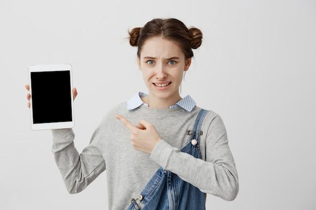 最新のデバイスを手に人差し指で身振りで示す動揺の感情を持つ女性のクローズアップ写真。欠陥のあるガジェットがオフになっているため、女性の若いデザイナーは作業できません。問題、失敗