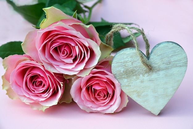 Closeup picture of pink roses with a heart-shaped wooden ornament