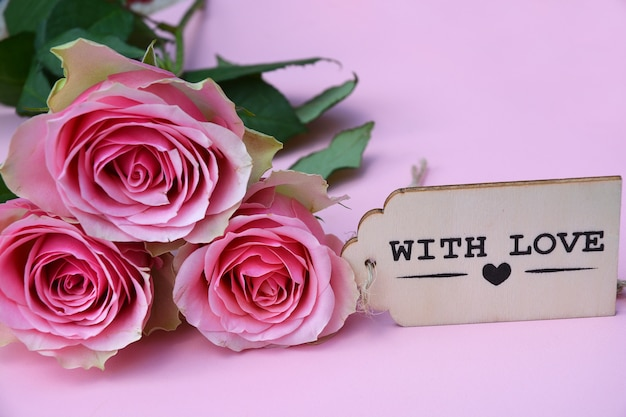 Closeup picture of pink roses  next to the wooden decoration against a pink background