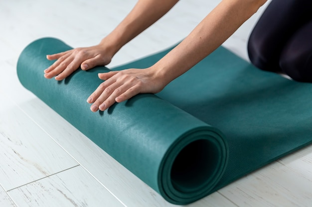 Closeup picture of yoga green mat. woman is getting ready for exercises indoor.
