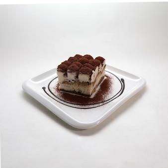Primo piano di un pezzo di tiramisù fresco e gustoso su un piatto bianco