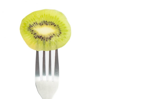 Closeup of a piece of kiwi on fork with copy space on white background