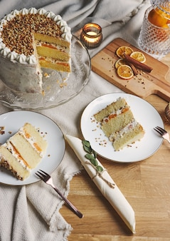 Closeup of pieces of white delicious cake with nuts and mandarine