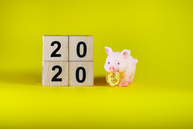 Closeup piggy bank standing with 2020 wooden block using as business financial planning concept