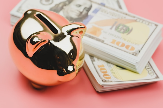 Closeup piggy banks and a house model with banknotes us dollars for saving to buy a house on pink wall. property investment and house mortgage financial.