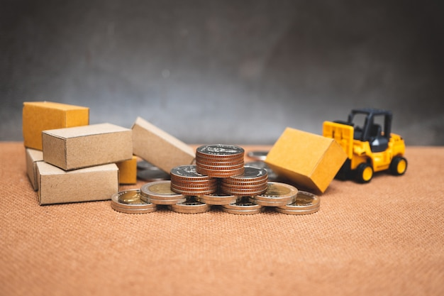 Closeup pile of coins with carton boxes and forklift vehicle