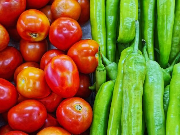 販売のための新鮮な赤いトマトと緑の唐辛子のクローズアップの山