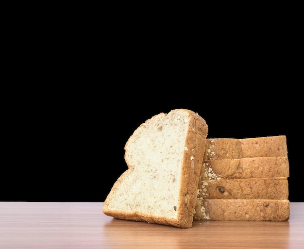 Closeup pile of wheat bread for breakfast on brown wood desk isolated on black background