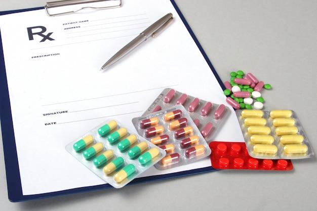 Closeup of a pils, stethoscope, pen onn rx prescription.