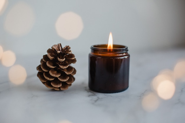 Closeup of pine cone and candle