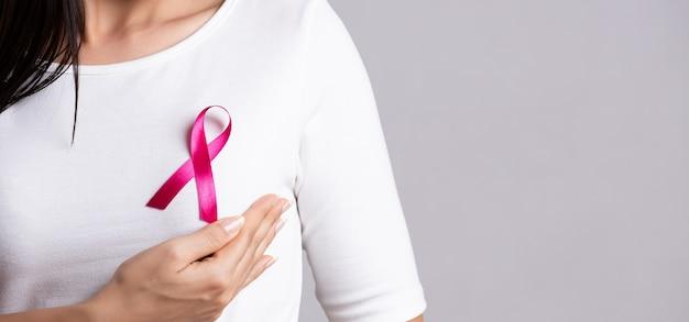Closeup of pink badge ribbon on woman chest to support breast cancer cause