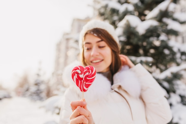 Closeup pink heart lollypop in hands winter woman chilling on street full with snow in sunny morning. white knitted hat, enjoying. delicious, sweet life, winter holidays.