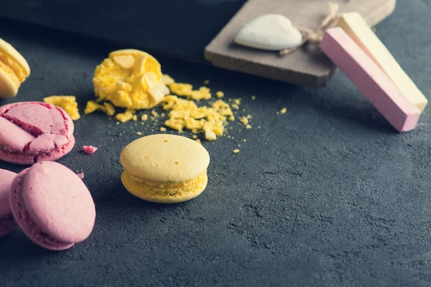 Closeup of pink macaroons on black concrete background