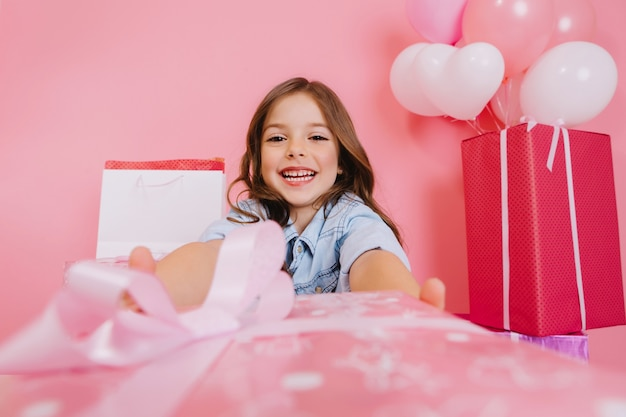Closeup pink present giving little joyful girl to camera on pink background. smiling suround big giftboxes, balloons, celebrating birthday party, expressing positivity