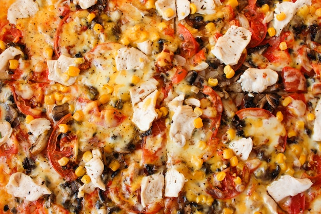 Closeup of pizza with chicken, tomatoes, corn, cheese, mushrooms and spices