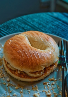 Closeup plain bagel with banana and peanut butter
